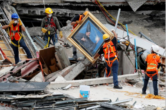 Mexican and international rescue teams remove a painting as they search for survivors in a collapsed building after an earthquake, at Roma neighborhood in Mexico