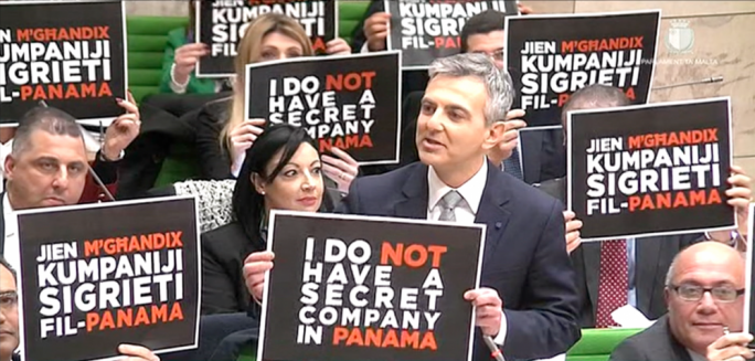 Opposition MPs hold placards in parliament reading 'I don't have a secret company in Panama'