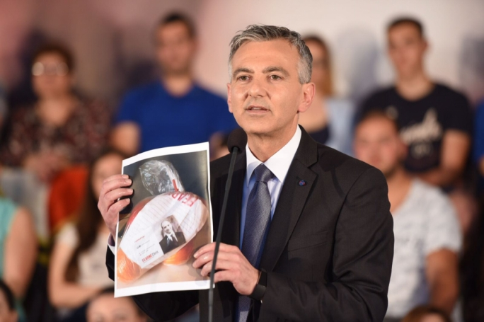 Busuttil holding up a bag of oranges being distributed by Chris Fearne in the fourth district