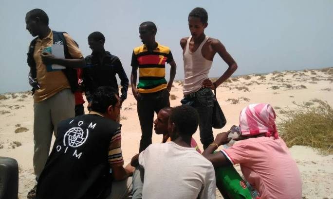 A group of Somali and Ethiopian people wait on a beach near Shabwa after being forced from a boat off the coast of Yemen