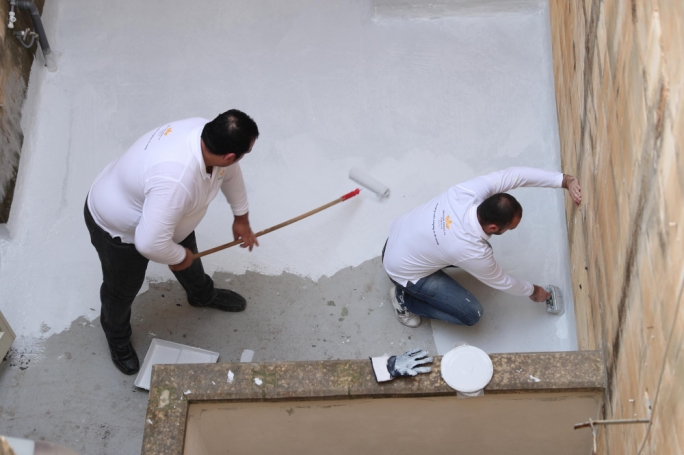 British American Tobacco Malta staff sealing the home's roofs against rainwater seepage