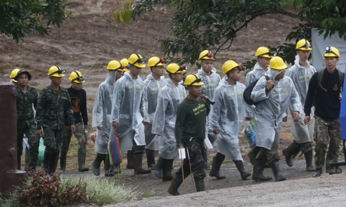 Rescuer workers walk toward the cave entrance in Mae Sai on Tuesday