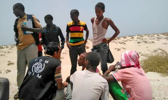 IOM staff assist migrants after they were forced into the sea by smugglers