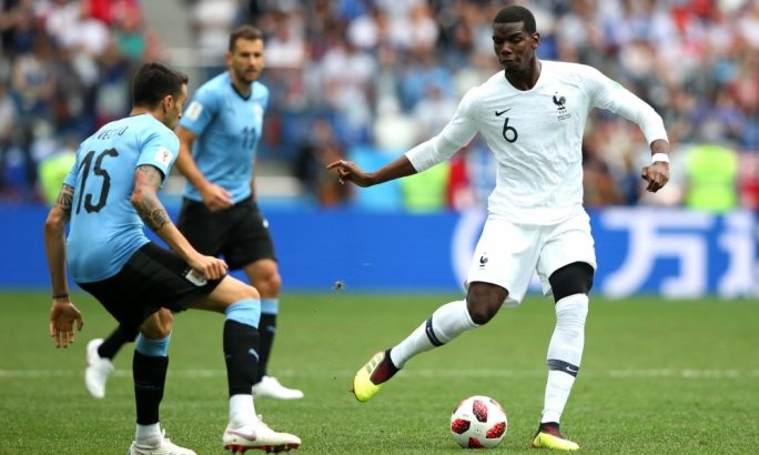 Maximiliano Pereira of Uruguay puts pressure on Paul Pogba