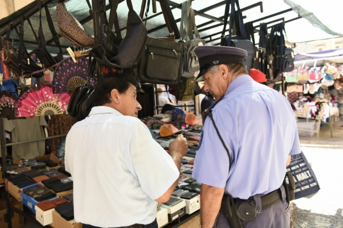 The GRTU want stricter enforcement on street vendors that do not have hawking permits. Photo shows a legal hawker on Ordnance Street speaking to a police officer.