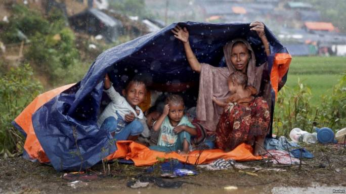 Rohingya refugees shelter from the rain in a camp in Cox's Bazar, Bangladesh (Photo: VOA News)