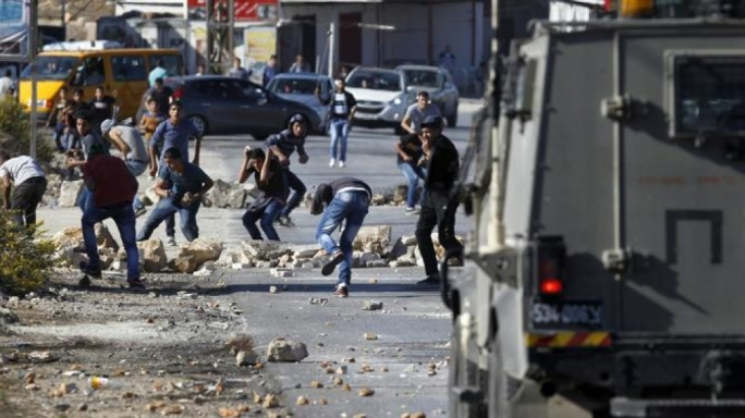 Palestinians from the Jalazoun refugee camp clash with Israeli security forces