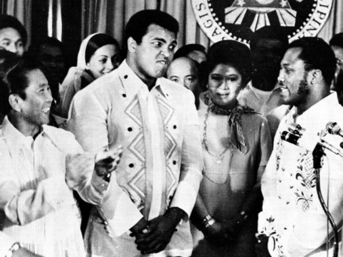 Philippines President Ferdinand Marcos, left, applauds as challenger Joe Frazier, right, makes some remarks about world champion Muhammad Ali, second from left, during their call on Marcos at the Malacanang Palace in Manila, Sept. 18, 1975