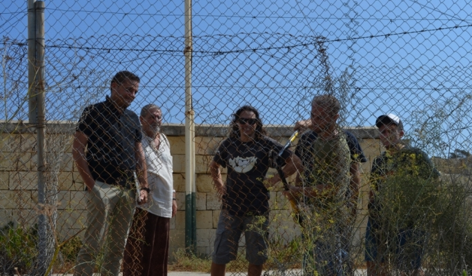 Gzira mayor Conrad Borg Manche and Salvu Mallia look on as KEA activists break through the fence