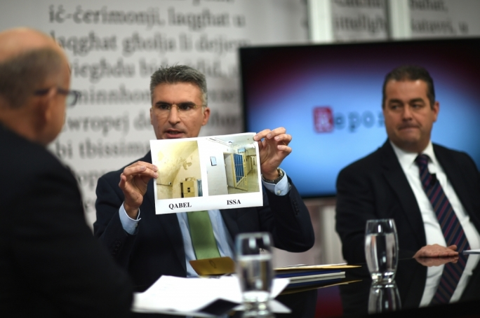 Minister Carmelo Abela displays pictures comparing current and past conditions of police lock-up. Photo: Ray Attard