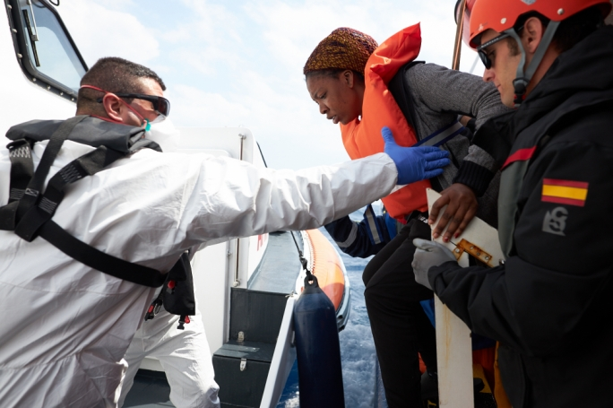 An AFM soldier assists the transhipment of people rescued at sea by the Sea-Eye ship Alan Kurdi