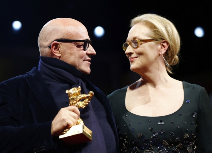 Gianfranco Rosi accepting the Golden Bear Prize from actress Meryl Streep at the Berlinale for his Lampedusa migration documentary Fuocoammare (Fire at Sea)