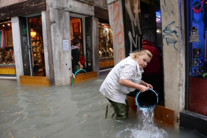 A woman removes water from her shop