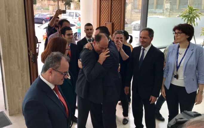 A tearful Godfrey Farrugia is embraced by PN whip David Agius outside the PN headquarters