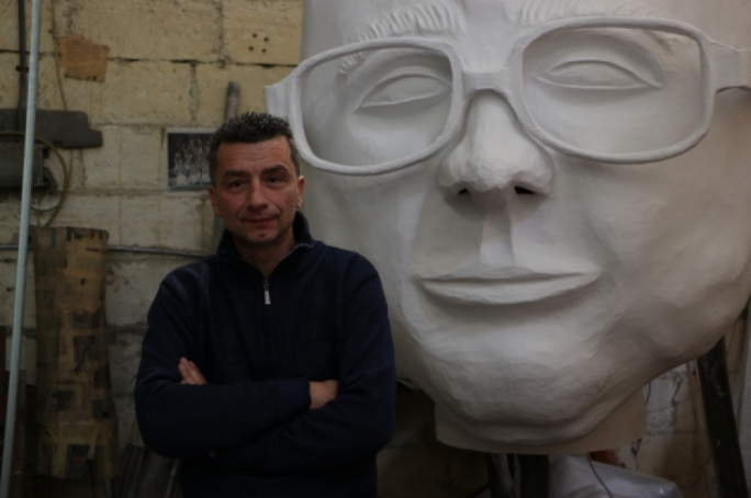 Float-maker Rayvin Galea with the giant effigy of Charles Scicluna, the centrepiece of his float