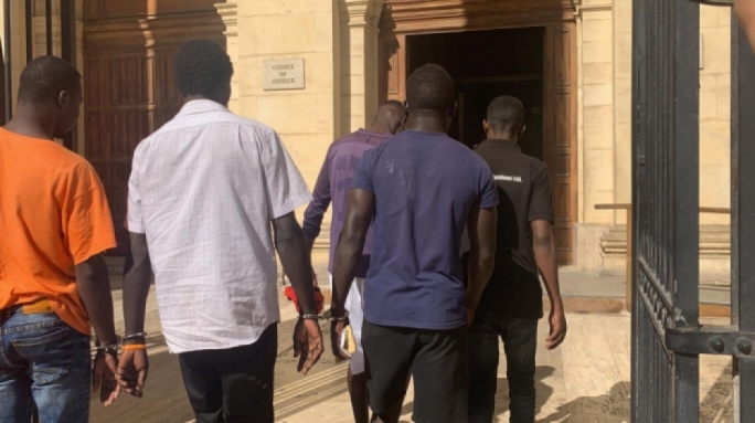 Handcuffed migrants brought to court after a protest at the Hal Far open centre in October