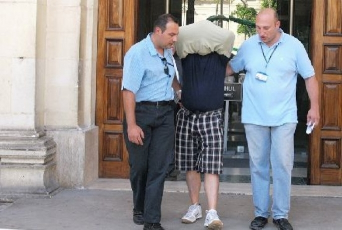 Photo from 2010: Vince Muscat 'il-Kohhu' is escorted from court after being charged with involvement in the 2010 HSBC heist