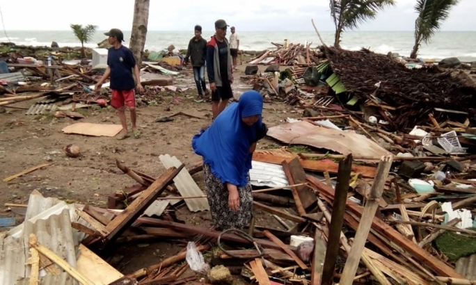 Surviving residents inspect the damage to their homes on Carita beach in South Sumatra, Indonesia