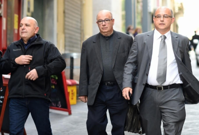 Fr Charles Fenech (centre) emerging from the law courts in Valletta in 2017, following his first sentencing (Photo: Ray Attard)