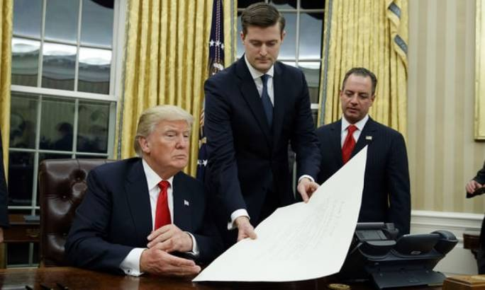 Rob Porter, centre, hands Donald Trump a document in the Oval Office in January 2017 (Photo: The Guardian)