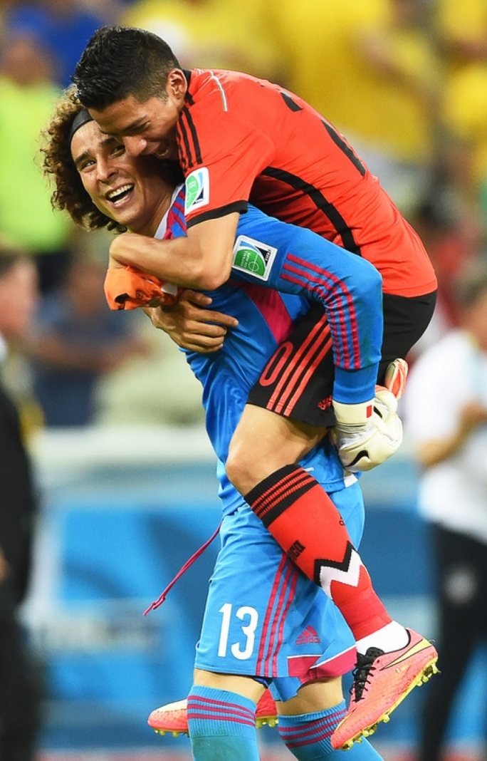 Mexico s goalkeeper Guillermo Ochoa (L) celebrates with his teammate  Giovani Dos Santos (up 57ff43950