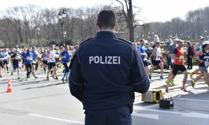 A German police officer stands guard during Berlin's half-marathon. (photo: The Guardian)