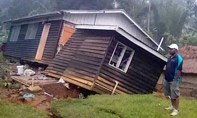 A local stands next to a damaged house near a landslide in the town of Tari (Photo: The Guardian)