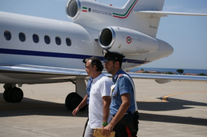 Mario Gennaro, handcuffed, escorted by the police on his arrival in Italy on Friday