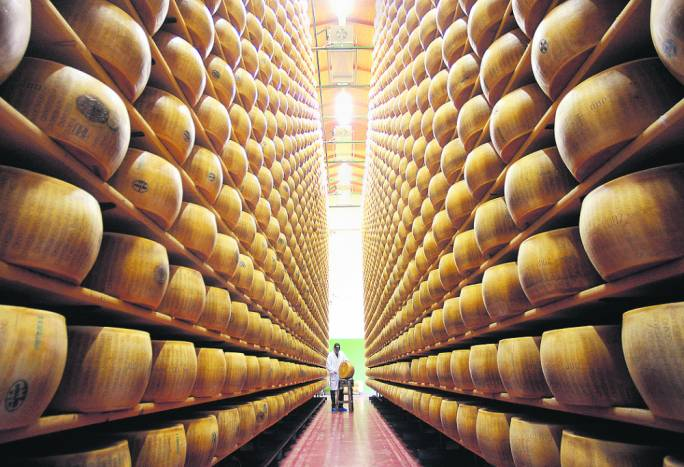 A Parmigiano-Reggiano consortium quality control chief checks a wheel of Reggiano cheese, in Bibbiano, Italy. Across Europe, dozens of food products - from Greek feta cheese to Britain's Jersey Royal potatoes - have EU trademark protection