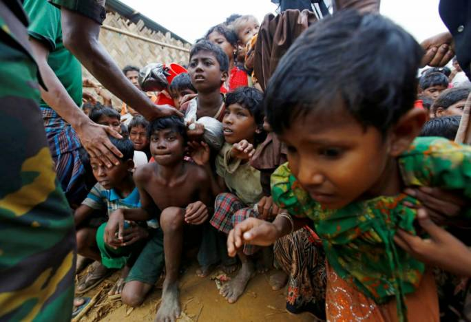 Rohingya refugee children struggle as they wait to receive food outside the distribution center at Palong Khali refugee camp near Cox's Bazar, Bangladesh (Photo: Al Jazeera)
