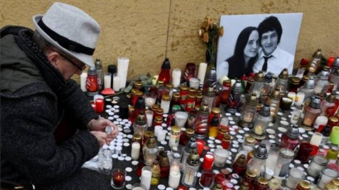 A man lights a candle as tribute for the murder of the journalist and his girlfriend (Photo: Reuters)
