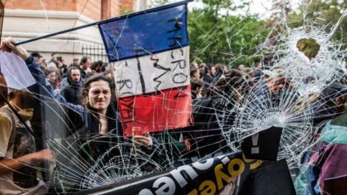 A protester holds the French flag with an anti-Macron slogan outside a destroyed McDonald's (Photo:BBC)