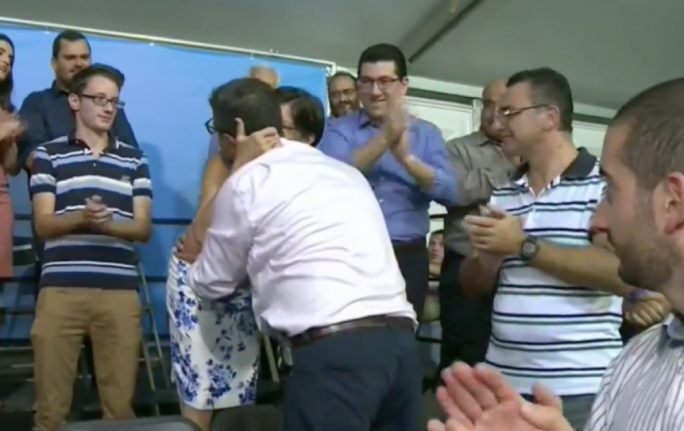 Close embrace: Maria Deguara whispers in Adrian Delia's ears during a round of hugs with MPs on Sunday's first appearance as party leader