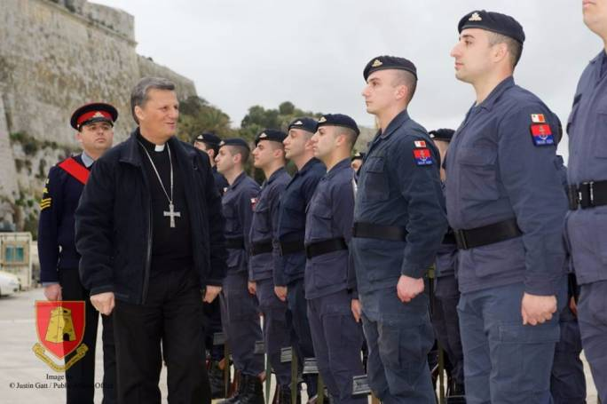 Bishop Mario Grech inspects personnel upon arrival at the AFM patrol boat base at Haywharf