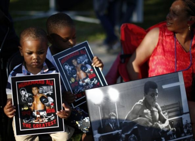 Brandon Liggons, 2, (L) holds an image of Muhammad Ali during the funeral procession for the three-time heavyweight boxing champion in Louisville, Kentucky, U.S., June 10, 2016.