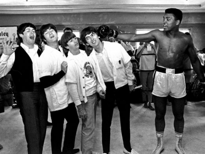 In this Feb. 18, 1964, The Beatles -- from left, Paul McCartney, John Lennon, Ringo Starr, and George Harrison -- take a fake blow from Cassius Clay, who later changed his name to Muhammad Ali, while visiting the heavyweight contender at his training camp in Miami Beach, Fla.