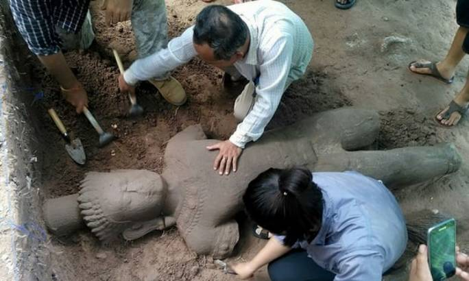 Archaeologists excavate a statue believed to have once stood guard over an ancient hospital at Cambodia's famed Angkor temple complex