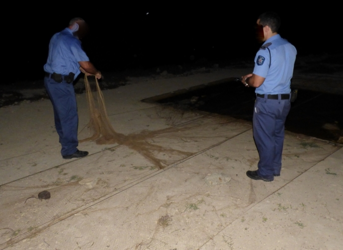 Police officers removing a clap net in Sarraflu
