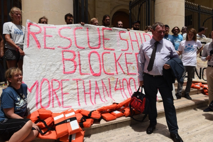 Lifeline captain Claus-Peter Reisch posing with activists from his ship outside the law courts in Valletta