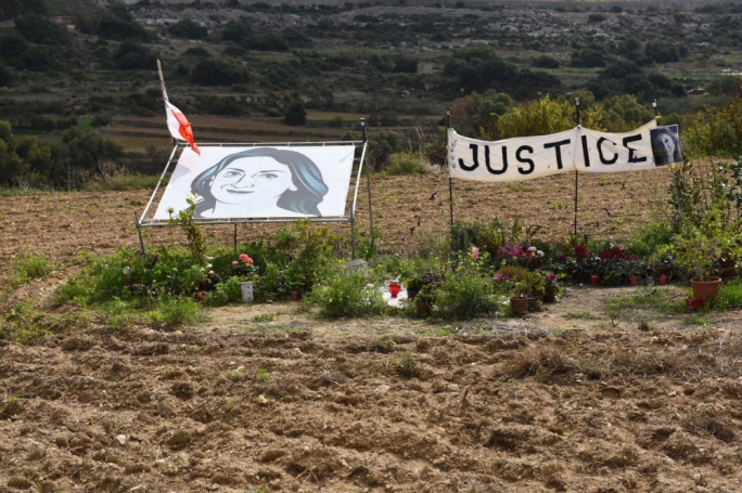 Two large banners mark the exact spot in a field, where Daphne Caruana Galizia's burning car stopped