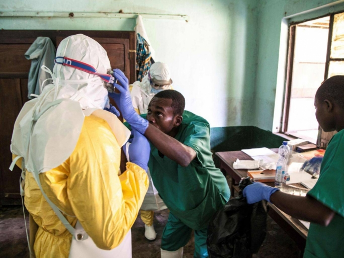 Health workers wear protective equipment before attending to patients. (Photo: Getty Images)