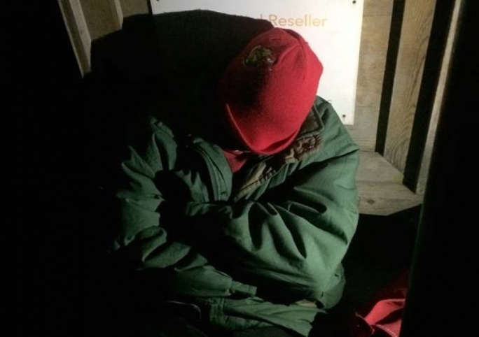 A migrant sleeps outside Evans Building to make sure he gets in at the identity card office once it opens on Friday morning.