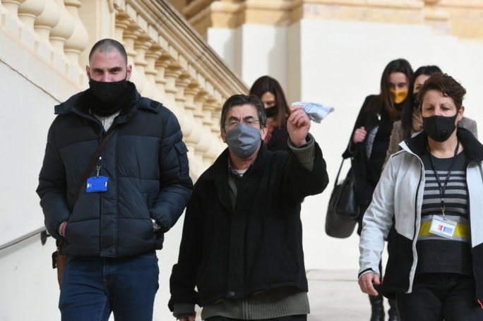 Fr Joseph Cini waved his handkerchief towards journalists as he was escorted by police out of the court building to be taken back to the Corradino Correctional Facility (Photo: James Bianchi/MaltaToday)