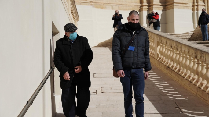 Fr Joseph Sultana (left) being accompanied by police to the waiting prison van after the court sitting was over (Photo: James Bianchi/MaltaToday)