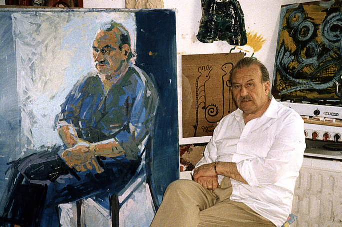 Gabriel Caruana in his studio seated next to a portrait by Lawrence Buttigieg.