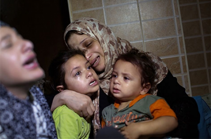The mother of three-year-old Saher Abu Namous mourns during his funeral after he was killed in an explosion