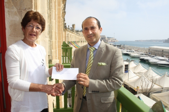 : Stephen Xuereb, CEO of Valletta Cruise Port presenting a donation to Jane Debono from Tomasina Cat Sanctuary