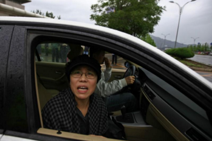 Liu Xia, wife of Liu Xiaobo, looks out of a car window after a trial outside a court in the Huairou district of Beijing in June 2013