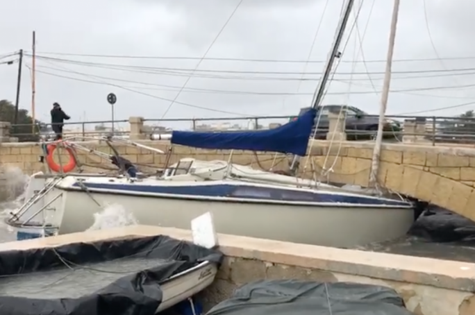 A sailing boat stuck under the bridge at Manoel Island as Marsamxett Harbour got battered by strong waves