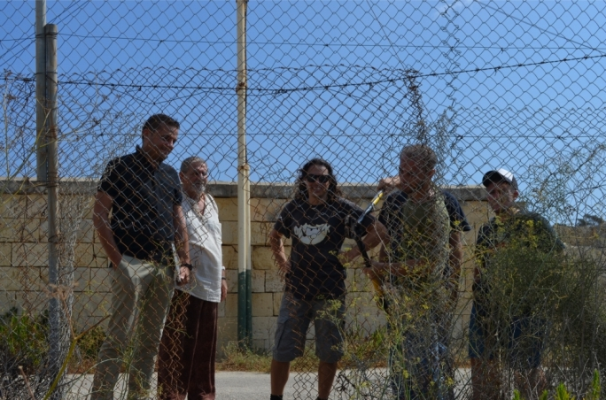 Gzira mayor Conrad Borg Manche and Salvu Mallia look on as KEA activists break through the fence